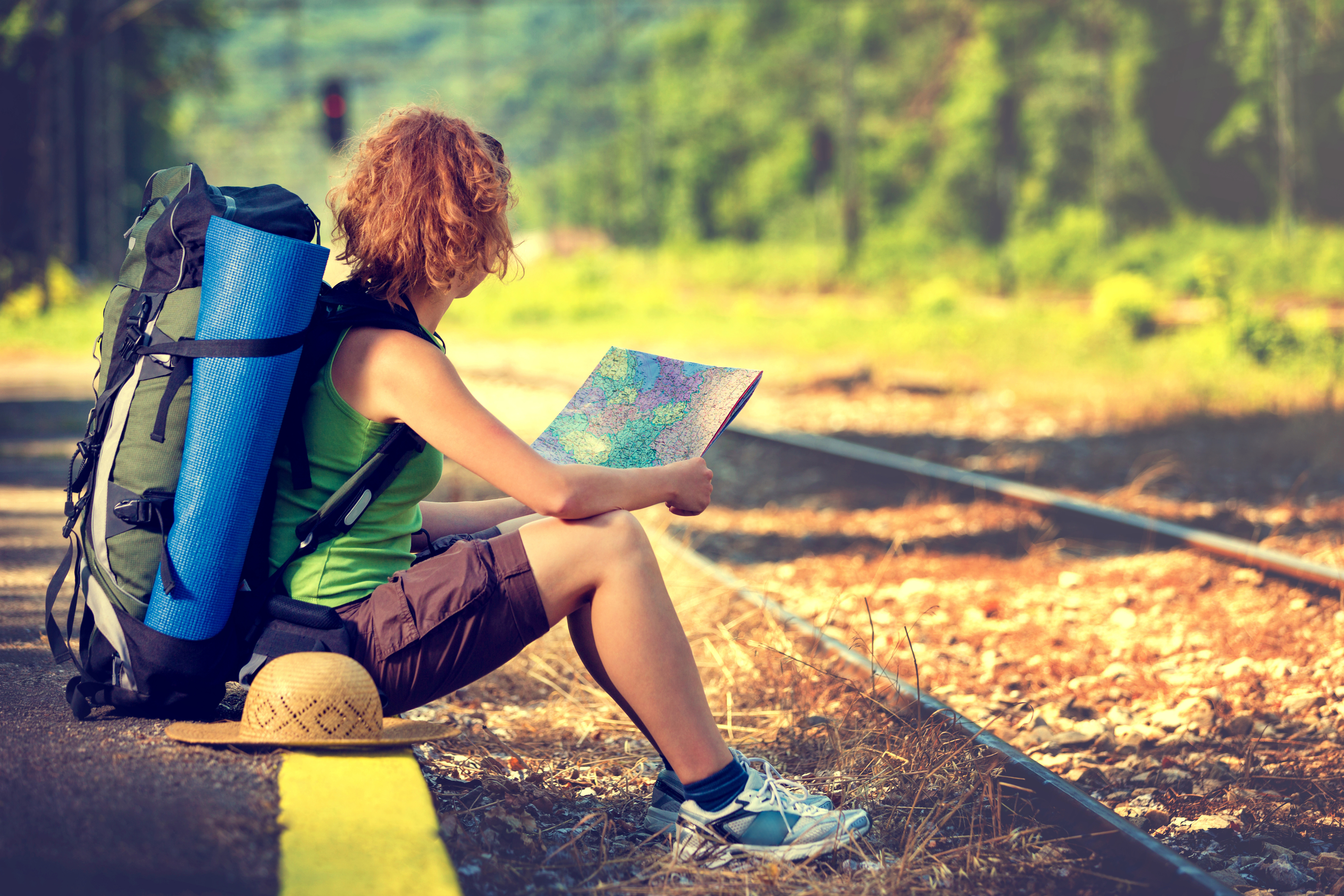 Girl wearing backpack and holding map, waiting for a train.