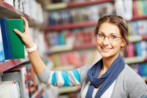 Portrait of pretty girl in library looking at camera with smile