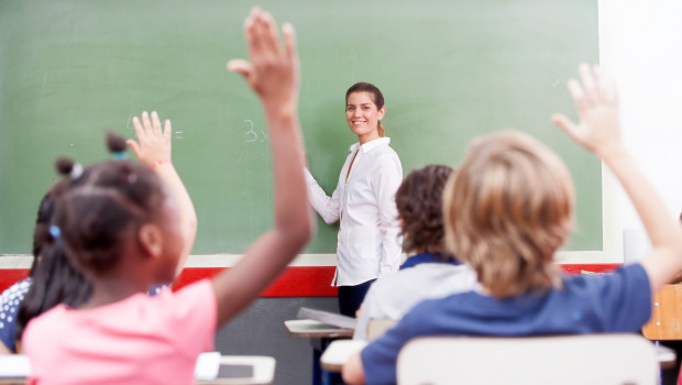 Happy schoolchildren at primary school raising hand in elementary multi ethnic classroom.