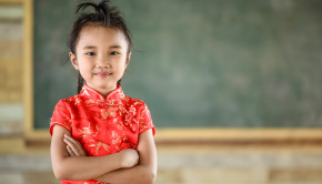 Little girl on red Chinese dress with chalkboard background